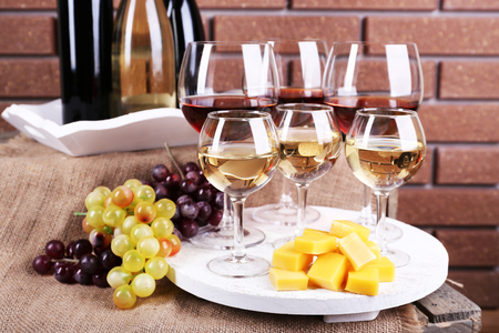 Bottles and glasses of wine, cheese and ripe grapes on table on brick wall background photo