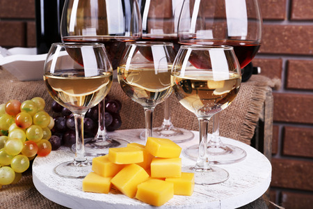 winy: Bottles and glasses of wine, cheese and ripe grapes on table on brick wall background