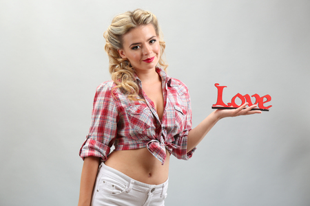 Beautiful girl with pretty smile in pinup style, on grey background