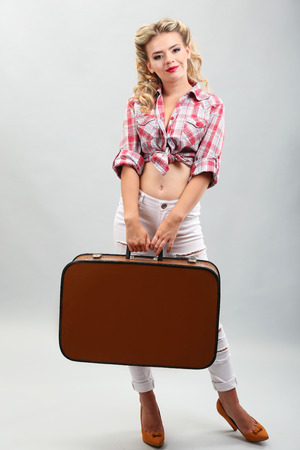 Beautiful girl with suitcase in pinup style, on grey background