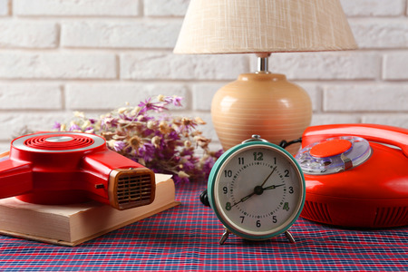 Retro things on table-hairdryer, clock, phone, book photo