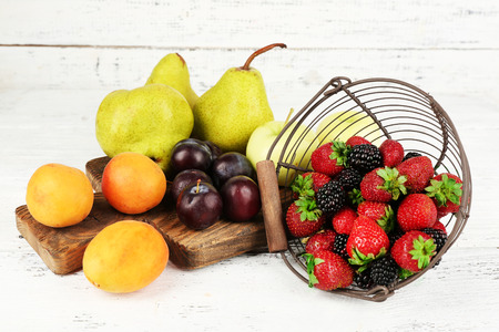 Ripe fruits and berries on table on wooden background photo