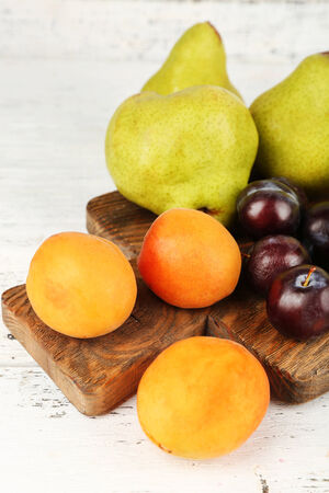 Ripe fruits on table on wooden background photo
