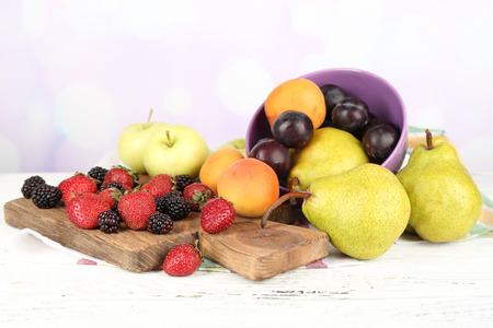 Ripe fruits in bowl and berries on table on bright background photo