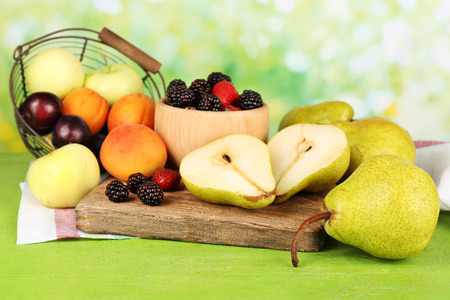 Ripe fruits and berries on table on bright background photo