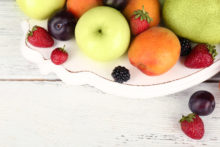 Ripe fruits and berries on table close up photo
