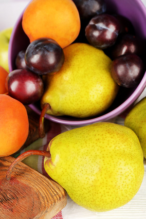 Ripe fruits in bowl on table close up photo