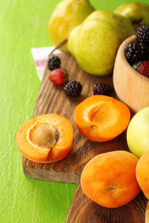 Ripe fruits and berries in bowl on table close up photo