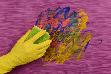 rubber gloves: Hand in glove wiping children drawing on wallpaper Stock Photo