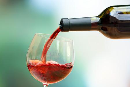 Vin rouge verser dans un verre à vin, close-up Banque d'images