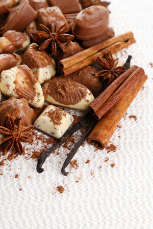 Different kinds of chocolates with spices on white background photo
