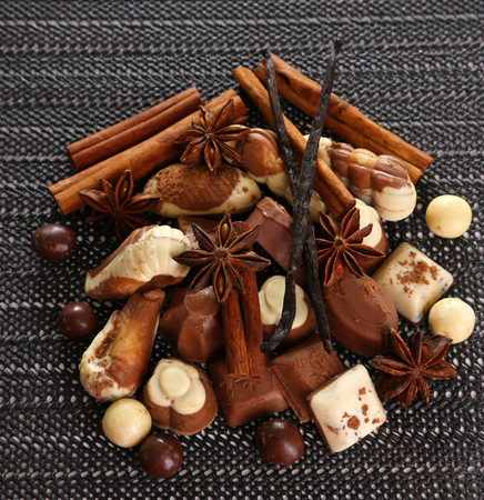 kinds: Different kinds of chocolates with spices on dark background