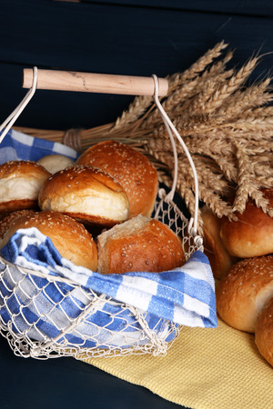 Tasty buns with sesame in  basket, on color wooden background photo