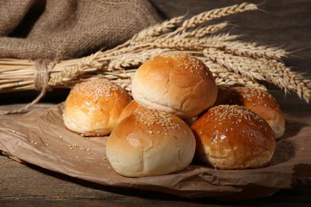 comiendo pan: Bollos sabrosos con s�samo sobre fondo de madera Foto de archivo