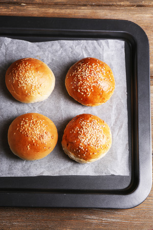 Tasty buns with sesame on oven-tray, on wooden background photo