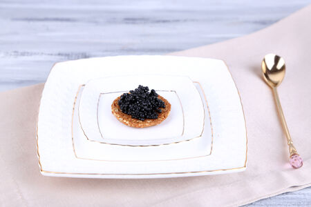 Black caviar on crispy bread on plate on napkin photo