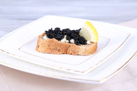 Slice of bread with butter, black caviar and lemon on plate on grey background photo
