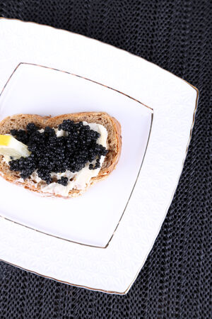Slice of bread with butter and black caviar on square plate on dark fabric background photo