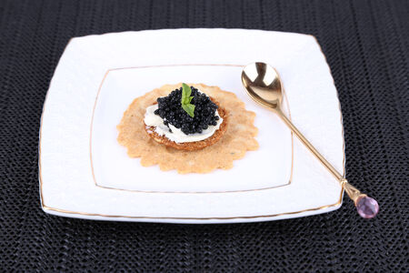 Black caviar with crispy bread on plate on dark fabric background photo