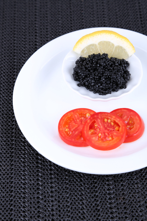 Black caviar with slices of tomato on plate on dark fabric background photo
