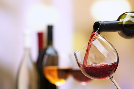 copa de vino: Vino rojo que vierte en copa de vino, primer plano