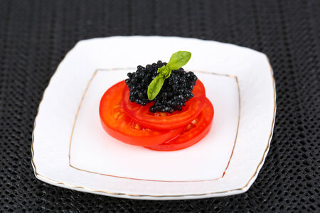 Slices of tomato with black caviar on plate on dark fabric background photo