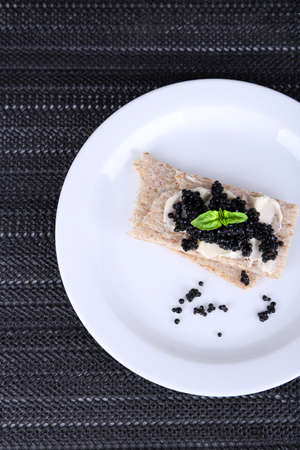 Slices of bread with butter and black caviar on plate on dark fabric background photo