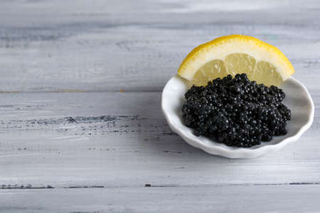 Black caviar with lemon on plate on grey wooden background photo