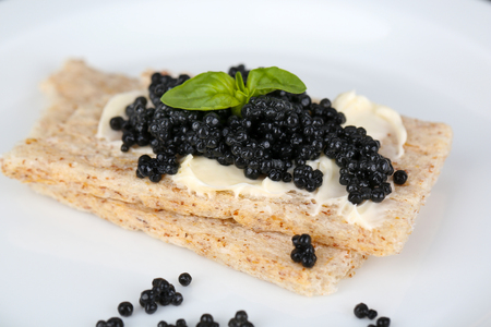 Slices of bread with butter and black caviar on plate closeup photo