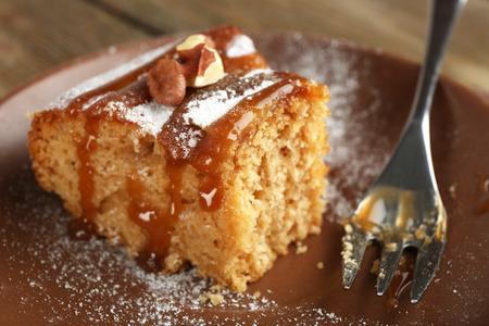 eaten: Half eaten delicious cake piece on plate on wooden table Stock Photo
