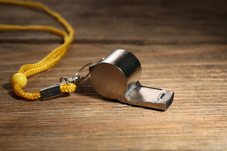 Sport metal whistle on wooden background Stockfoto