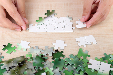 combined: Hand holding puzzle piece on wooden table background