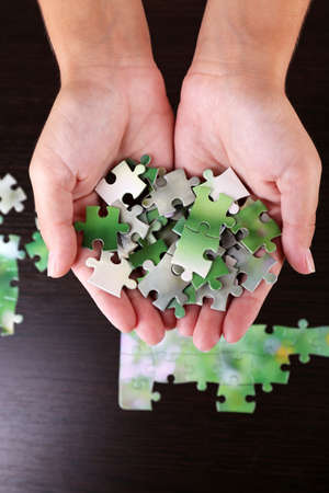 combined: Puzzle piece in hands on wooden table background