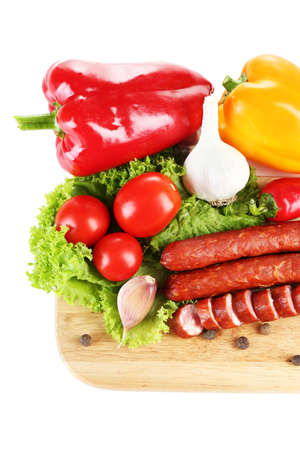 Smoked thin sausages and vegetables on cutting board, isolated on white photo