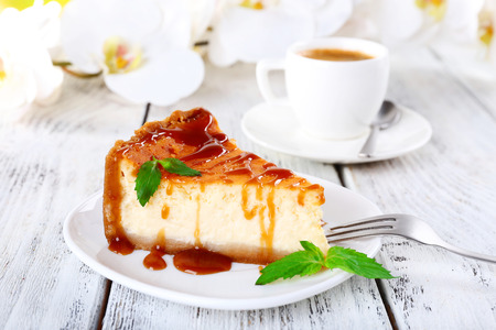 Cheese cake, orchids and cup of coffee on wooden background photo
