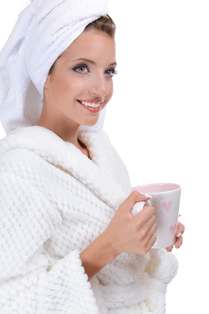 Beautiful young girl in bathrobe with cup of coffee isolated on white
