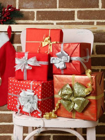 Christmas presents on chair on brown brick wall background photo