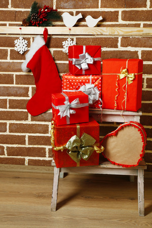 Christmas presents on white chair on brown brick wall background photo
