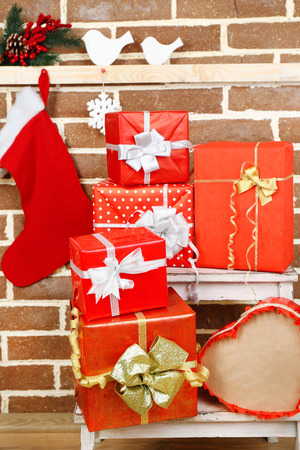 Christmas presents on stand ladder on brown brick wall background photo