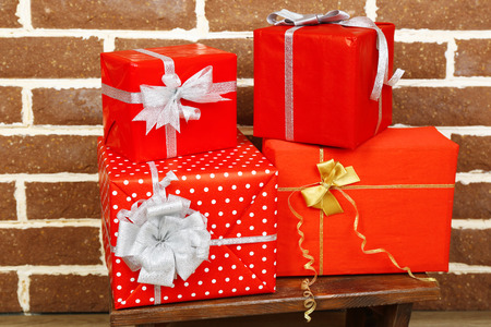 Christmas presents on stool on brown brick wall background photo