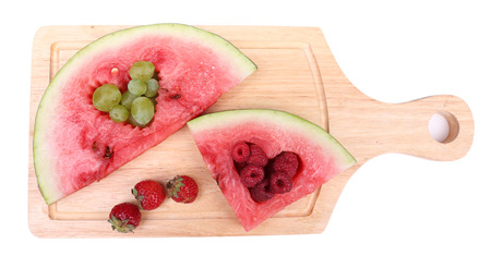 filled out: Fresh juicy watermelon slice  with cut out heart shape, filled fresh berries, on cutting board, isolated on white