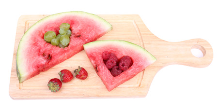 Fresh juicy watermelon slice  with cut out heart shape, filled fresh berries, on cutting board, isolated on white photo