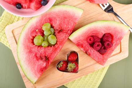 filled out: Fresh juicy watermelon slice  with cut out heart shape, filled fresh berries, on cutting board, on wooden background