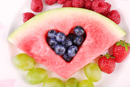 filled out: Fresh juicy watermelon slice  with cut out heart shape, filled fresh berries, on plate, close-up