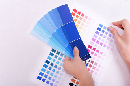swatches: Woman choosing color for wall from swatches in room