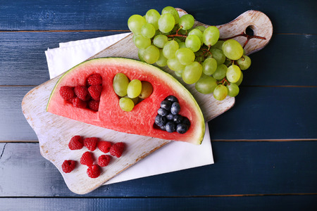 filled out: Fresh juicy watermelon slice  with cut out heart shape, filled fresh berries, on cutting board, on color wooden background