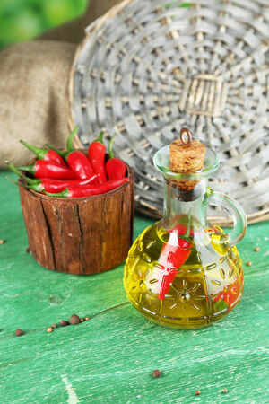 Homemade natural infused olive oil with red chili peppers in bottle on color wooden table, on bright background photo