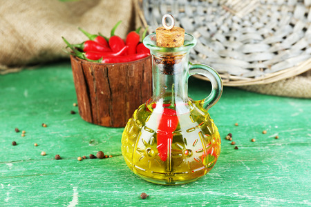 Homemade natural infused olive oil with red chili peppers in bottle on color wooden background photo