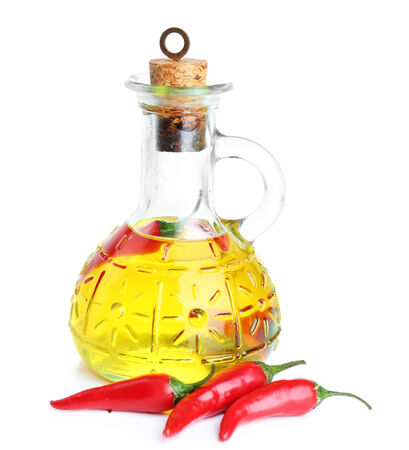 Homemade natural infused olive oil with red chili peppers isolated on white photo