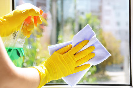 Cleaning windows with special rag and cleaner Stockfoto